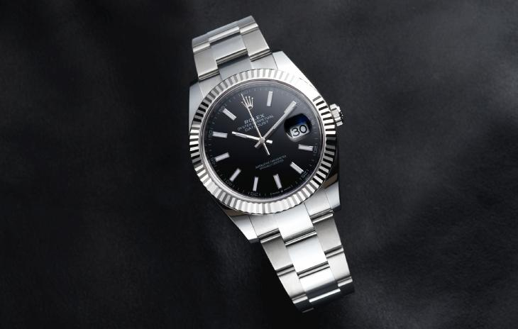 Rolex Oyster Perpetual Datejust II with black dial, stick markers, and fluted bezel