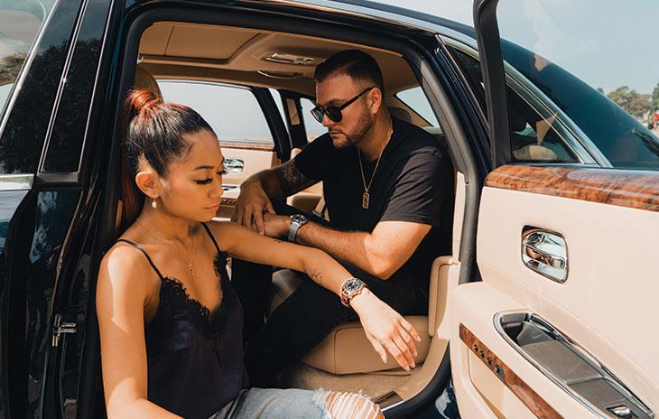Danica Janae wearing a Tudor Black Bay GMT and Kyle Car wearing a Breitling Superocean inside of a Rolls Royce.