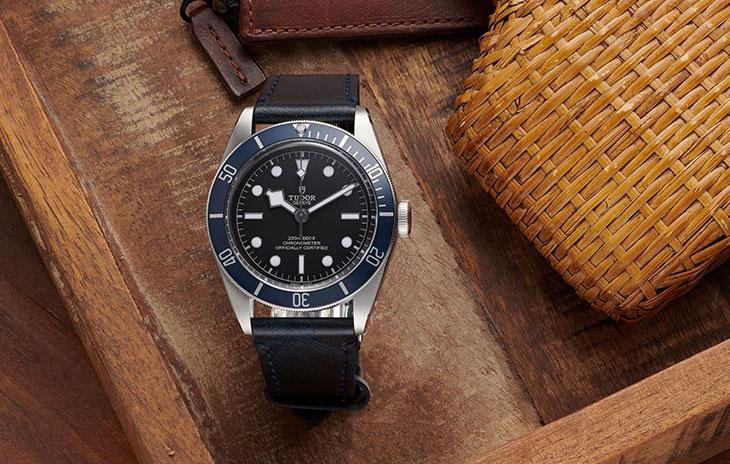 Tudor Black Bay with blue bezel, black dial, and blue leather strap on a wooden tray.