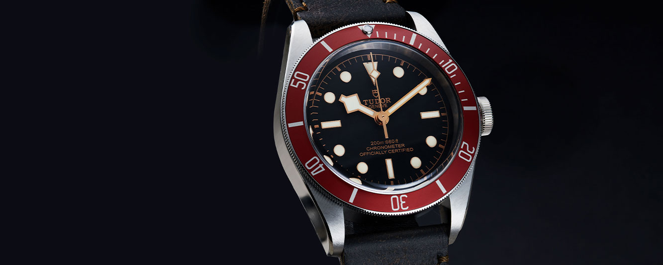 Tudor Black Bay with a red bezel and brown leather strap