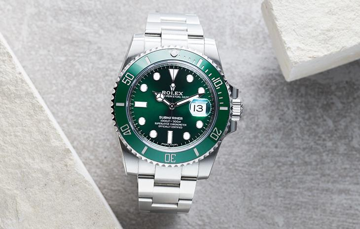 Rolex Submariner Date with a green bezel, green dial, and oyster bracelet.