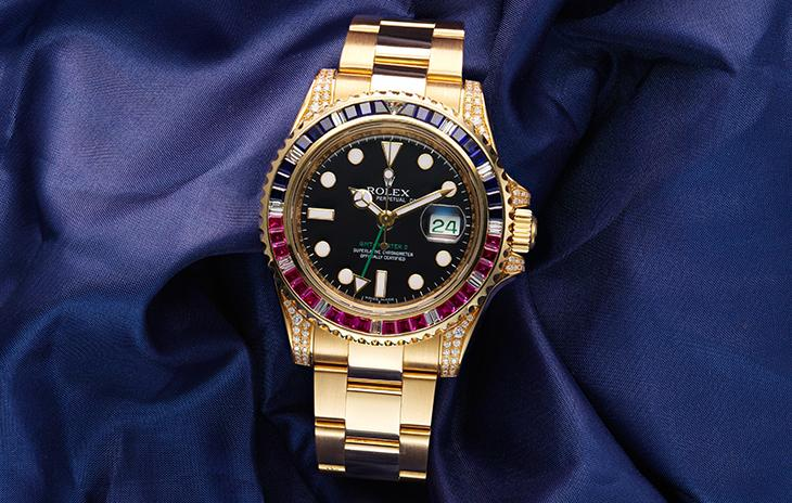 Rolex Submariner in yellow gold, set with blue gems, pink rubies, and diamonds.
