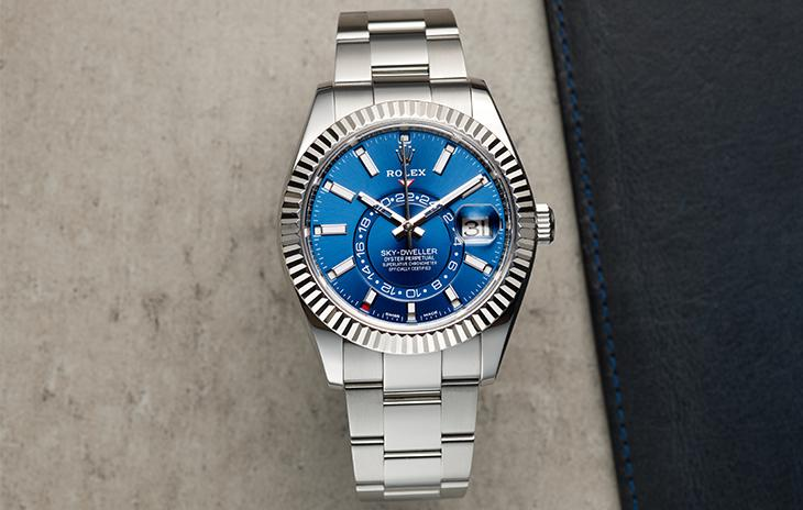 Rolex Sky-Dweller with blue dial, fluted bezel, and stick hour markers